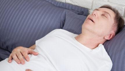 śpiący mężczyzna śpi na plecach i ma problemy z bebechem sennym